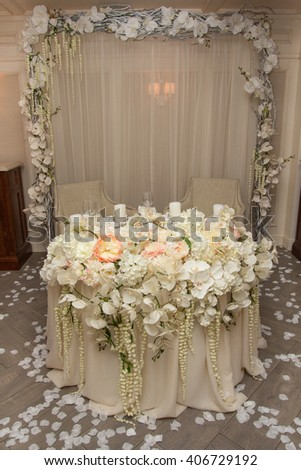 Wedding Table Decoration. Table set for a wedding dinner. Beautiful flowers on table in wedding day. - stock photo