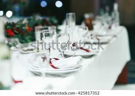 Wedding table set with white napkins and red ribbons - stock photo