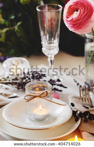 Wedding table setting. Dining table setting at Provence style with candles, lavender, vintage crockery and cutlery, closeup - stock photo