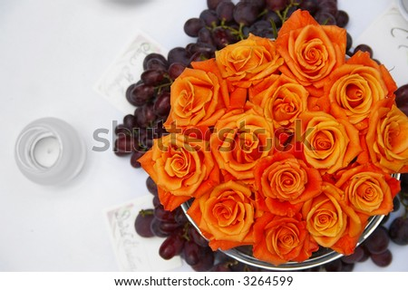 Wedding table setting from above with orange roses and grapes - stock photo
