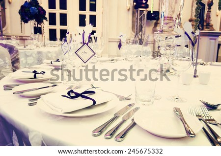 Wedding table setting in gorgeous banquet hall, toned yellow - stock photo