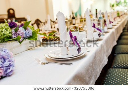Wedding table with meal drinks and decorations in restaurant.