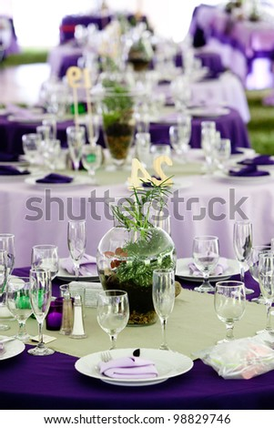 Wedding tables set up for fine dining in Green and Purple, unique centerpieces. - stock photo