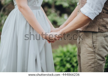 Wedding. The bride in a white dress and groom in a waistcoat standing and holding hands in the green garden