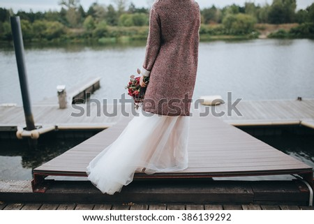 Wedding. The bride's bouquet. Wedding bouquet . The bride in a white dress standing on a pier at the lake and holding a bouquet of red and pink flowers with berries and greens with a marsala ribbon