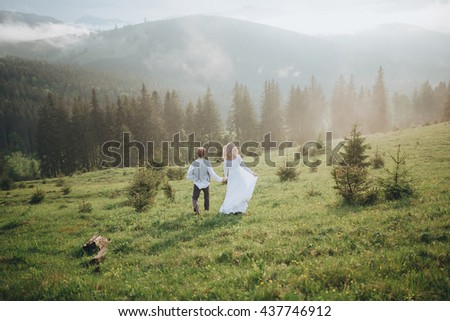 Wedding. The guy in the white shirt and waistcoat, and a girl in white dress walk on the green glade in the mountains