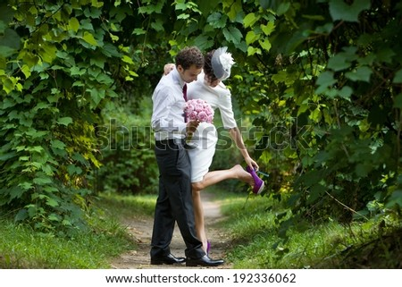 Wedding theme. A bride adjusting her shoe in the arms of a groom. Newlyweds in the botanical garden. - stock photo