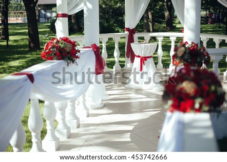 Wedding. Wedding ceremony. Arch.Rotunda. Aisle, decorated with red and white cloth standing in the woods to ceremony table, in the wedding ceremony area