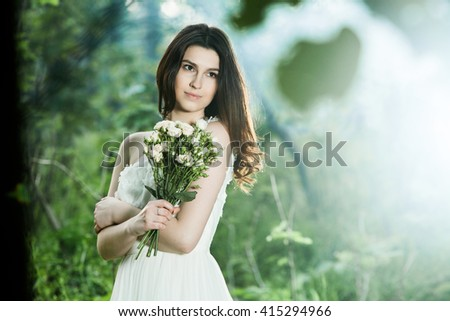 wedding: young bride posing in her wedding day Beautiful girl on the nature. Young beautiful bride in white dress on nature