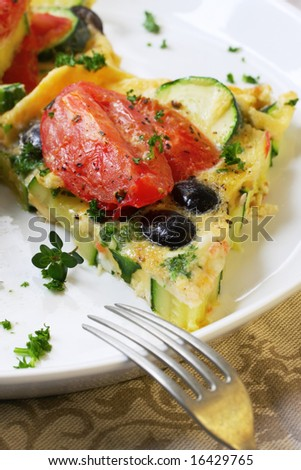 Wedge of vegetable frittata.  With Roma tomatoes, zucchini or courgette, black olives, eggs, garnished with parsley and thyme.  Italian style omelette.