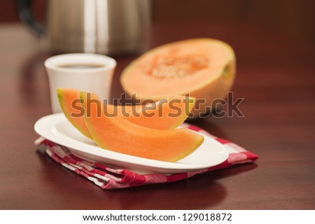Wedges of fresh cantaloupe served with coffee.