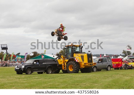 WEEDON, UK - AUGUST 28: One of the riders of the stunt duo, Kangaroo Kid, team jumps his ATV over a line of parked cars and an earth mover at the Bucks County show on August 28, 2014 in Weedon