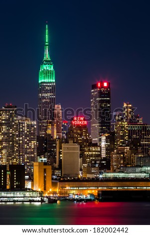 WEEHAWKEN, NJ, UNITED STATES - MARCH 16, 2014: Empire State Building by night. The top of the iconic skyscraper is lit in green in honor of Saint Patrick's Day.