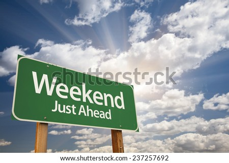 Weekend Just Ahead Green Road Sign with Dramatic Clouds and Sky. - stock photo
