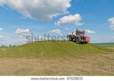 Weeled tractor rams green silo heap on blue sky background.