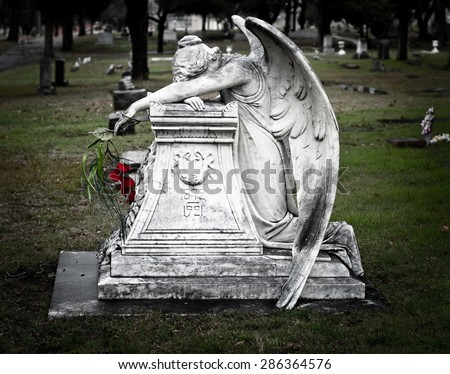 Weeping Angel with Red Flowers - stock photo
