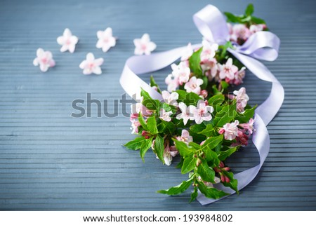 Weigel beautiful pink flowers on wooden table - stock photo
