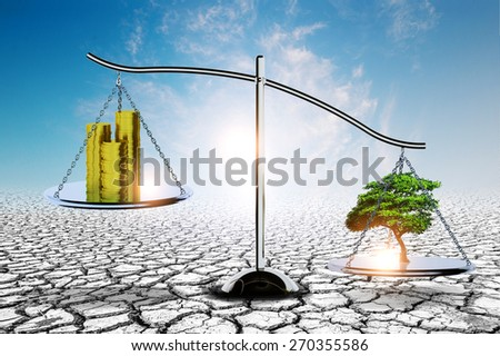 weighing scales with money and tree on soil crack background .Earth day Concept - stock photo