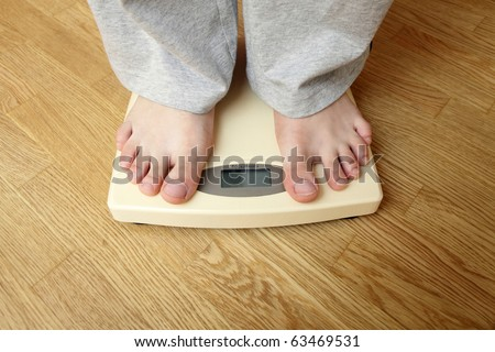 Weighloss - young man on a weighing scale - stock photo
