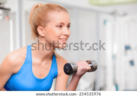 Weight exercise. Beautiful young woman in sports clothing exercising with dumbbells and looking away while standing in health club