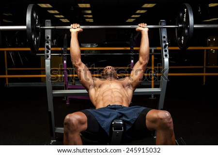 Weight lifter at the bench press lifting a barbell on an incline bench - stock photo