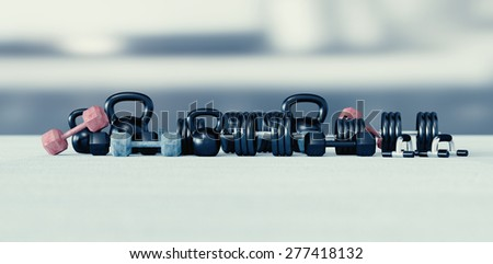 Weight lifting equipment: dumbbells, barbell, kettlebells, iron dumbbells, push up handles on a light background. - stock photo