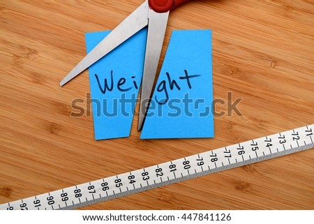 weight loss and dieting concept - cutting weight and measuring tape - stock photo