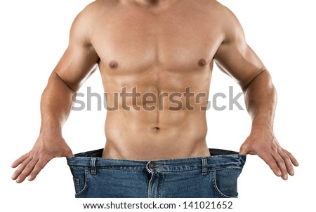 Weight loss, close up of muscular built man wearing too large jeans isolated on white background - stock photo