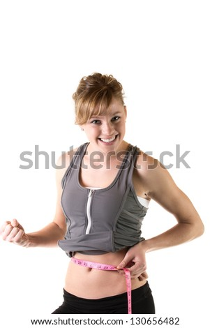 Weight loss concept - Excited young woman measuring her waist with tape. Isolated on white
