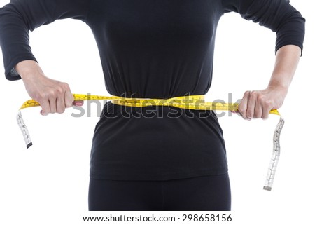 Weight loss concept, the woman in black tries to reduce her waist by measuring tape on white background. - stock photo