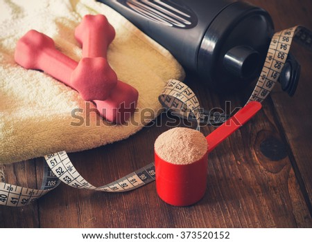 weight loss concept with tape measure whey powder, pink dumbbells and black shaker - stock photo