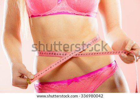 Weight loss, healthy lifestyle concept. Closeup measuring tape on woman body, fit girl wearing pink lace lingerie measuring her waistline - stock photo