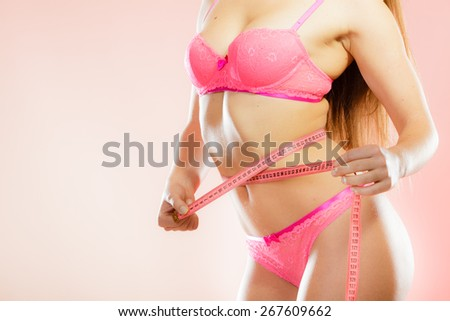 Weight loss, healthy lifestyle concept. measuring tape on woman body, fit girl wearing pink lace lingerie measuring her waistline - stock photo
