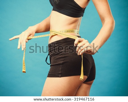 Weight loss, slim body, healthy lifestyle concept. Fit fitness girl measuring her waistline with measure tape on blue - stock photo