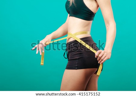Weight loss, slim body, healthy lifestyle concept. Fit fitness girl measuring her waistline with measure tape on green - stock photo