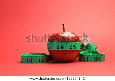 Weight loss slimming diet concept, New Year Resolution, with green measuring tape around a bright red apple, set against a red background. - stock photo