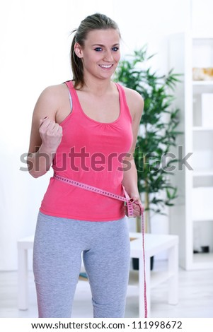 weight loss woman smiling happy excited standing with measuring tape - stock photo