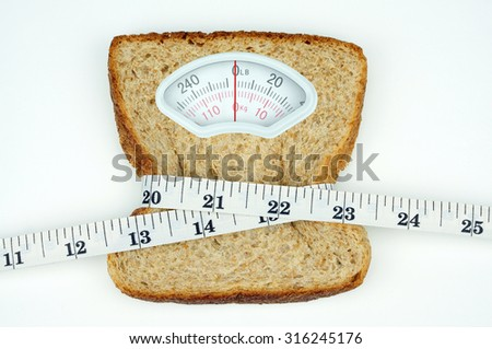 Weight scale with wholesome slice of bread and measuring tape on white background - stock photo