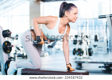 Weight training. Side view of confident young woman exercising with dumbbells in gym - stock photo
