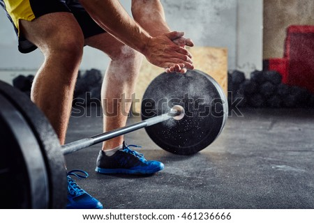 Weightlifter clapping hands before workout with barbell at the gym