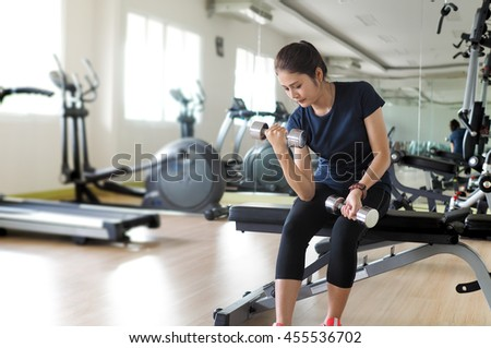 Weights training, Asian woman in fitness gym lifting weights workout strength body. - stock photo
