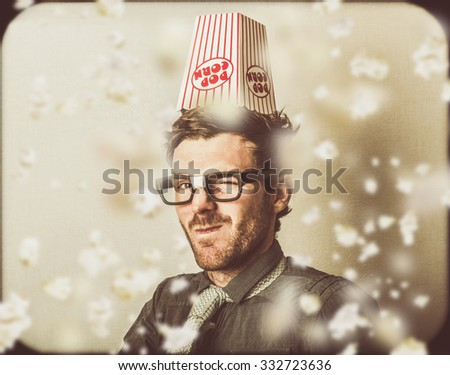 Weird geek winking under a shower of falling cinema popcorn when watching funny film. Comedy movie - stock photo