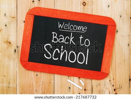 Welcome Back to school written in chalkboard on wood background - stock photo