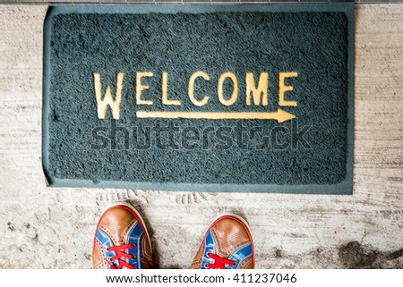Welcome Carpet with Colorful Sneakers on it - stock photo
