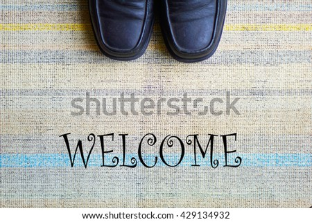 Welcome carpet with leather shoes on it. - stock photo