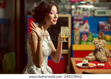 Welcome concept. Portrait of doll like brunette girl with retro hairdo in white trendy vintage polka-dot sleeveless dress drinking tea, saying hello. Close up. Copy-space. Indoor shot - stock photo