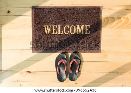 Welcome Doormat on wooden floor - stock photo