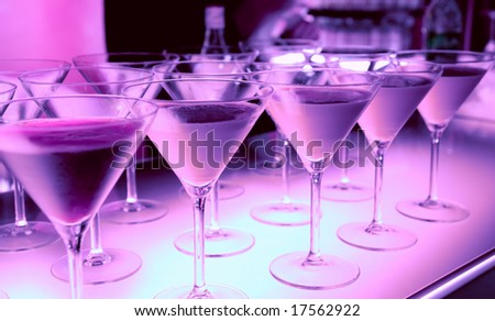 Welcome drink in a night club cocktails on illuminated bar counter - stock photo