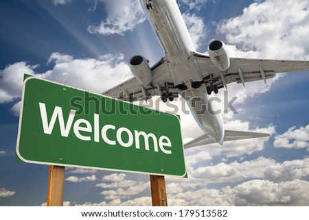 Welcome Green Road Sign and Airplane Above with Dramatic Blue Sky and Clouds. - stock photo