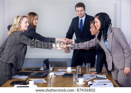 Welcome handshake before business meeting, 5 young business people at conference table - stock photo